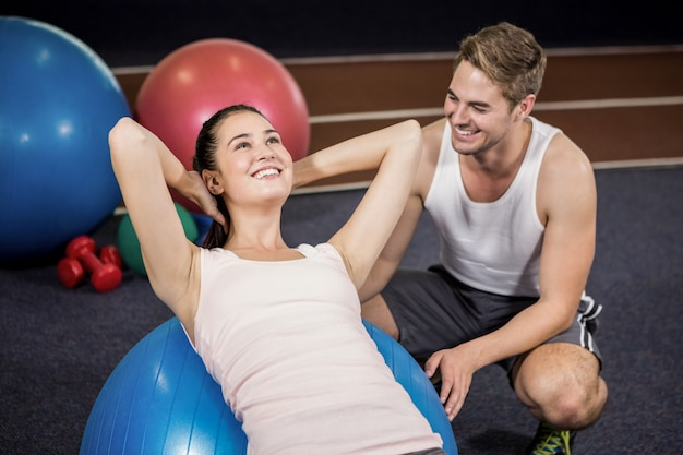 Trainer assisting a woman doing abdominal crunches on fitness ball Premium Photo