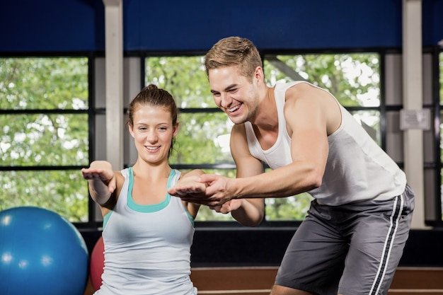 Trainer assisting woman with abdominal crunches Premium Photo