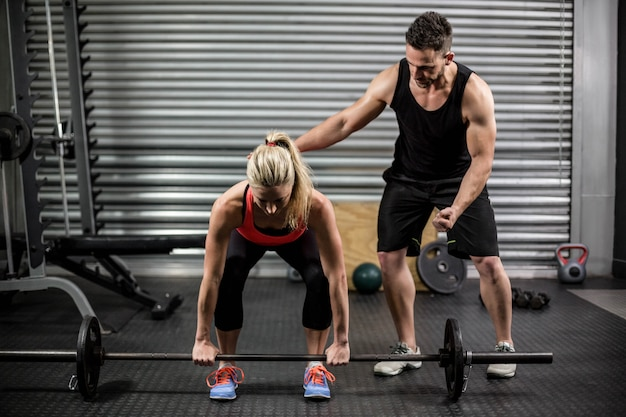 Trainer helping woman with lifting barbell at  gym Premium Photo