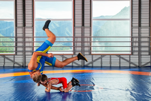 A trainer in sports wrestling tights teaches a little wrestler boy Premium Photo