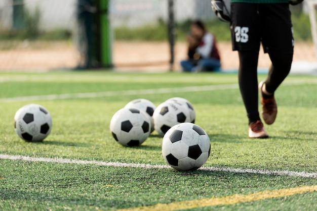 Training ball in green soccer field Premium Photo