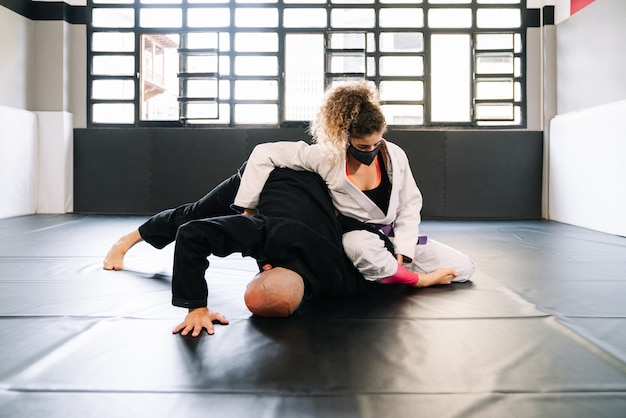 Training martial arts and judo with kimonos on the gym floor mat with a face mask because of the covid 19 Premium Photo