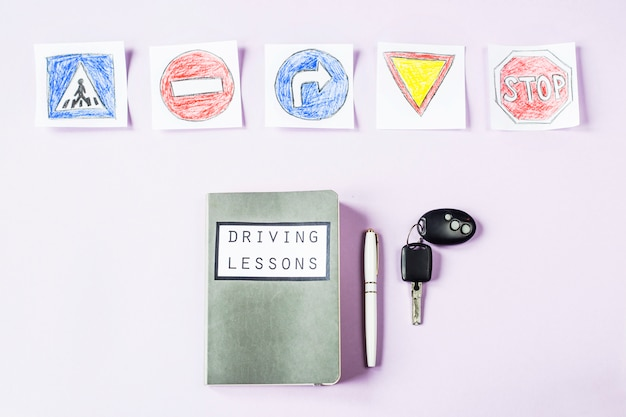 Training notebook for driving lessons and driving traffic rules next to the road sign drawings to get a driving license Premium Photo