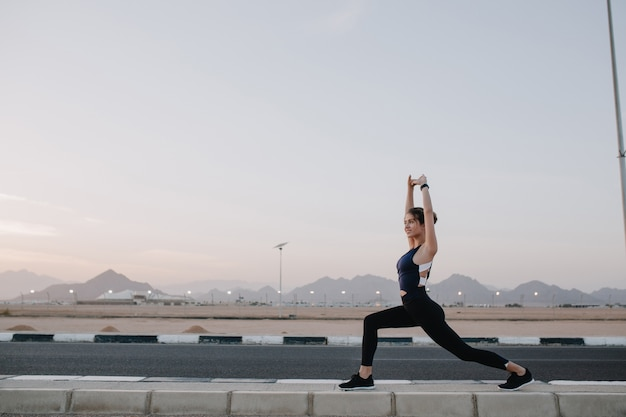 Training time, stretching on road in tropical country of joyful beautiful woman in sunny morning. workout of strong sportswoman, energy, motivation, healthy lifestyle.. Free Photo