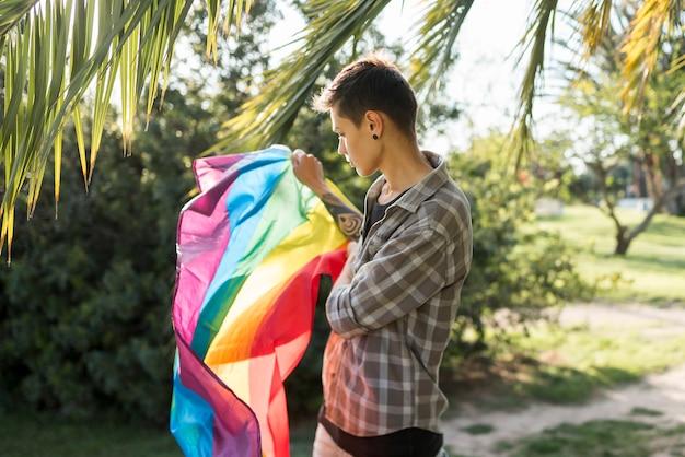 Transgender keeping lgbt flag in park Free Photo