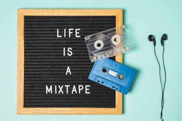 Прозрачная и синяя кассетная лента на доске объявлений с наушниками на бирюзовом фоне Бесплатные Фотографии