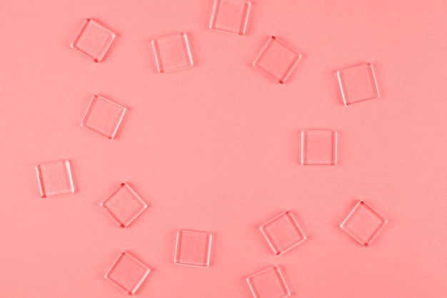 Transparent cubes arranged in circle shape against coral backdrop Free Photo