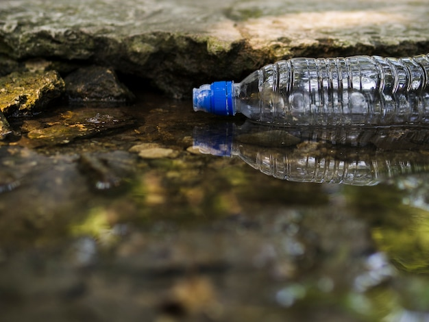 Transparent empty plastic water bottle floating on water Free Photo