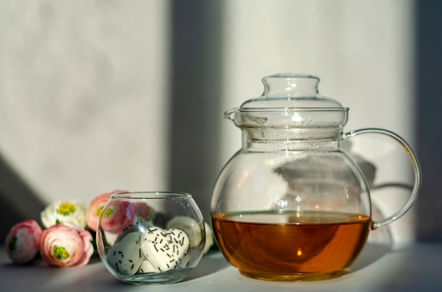 Transparent glass teapot with green tea, cookies in heart shape and flowers on the morning sunlight rays. Premium Photo