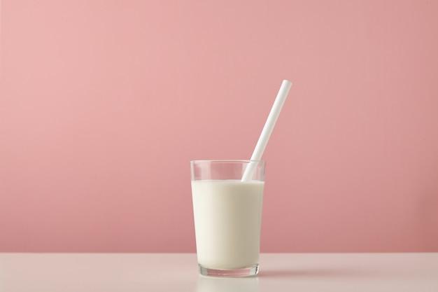 木製のテーブルのパステルピンクの背景に分離された新鮮な有機牛乳と白いストローと透明なガラス 無料写真