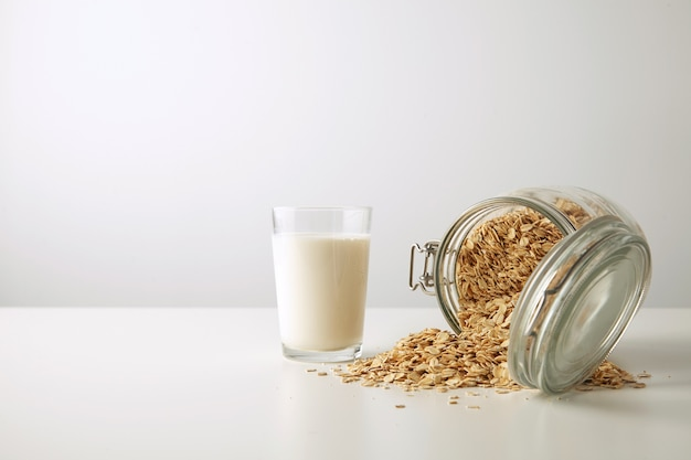 Transparent glass with fresh organic milk near lying half opened rustic jar with rolled oats spread out isolated in center on white table side view Free Photo