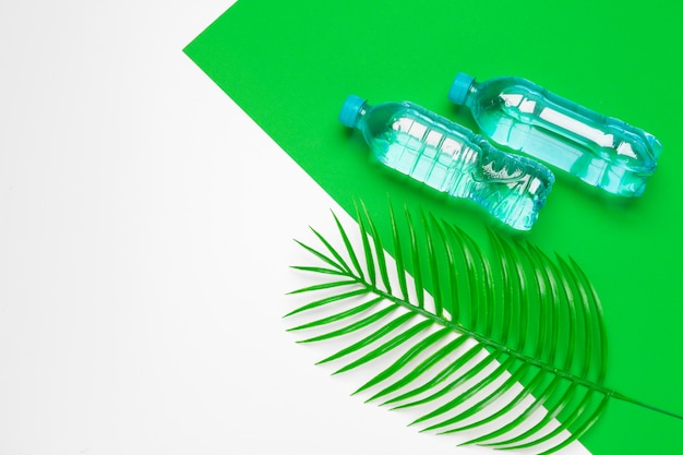Transparent liquid bottle with tropical palm leaves, top view background Premium Photo