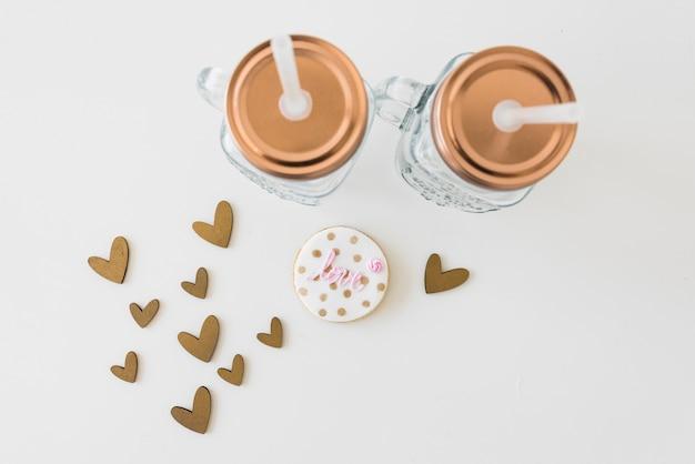Прозрачная каменщик с любовным печеньем и сердечками на белом фоне Бесплатные Фотографии