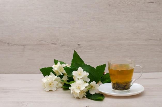 Transparent mug with green tea, a sprig of jasmine on the wood Premium Photo