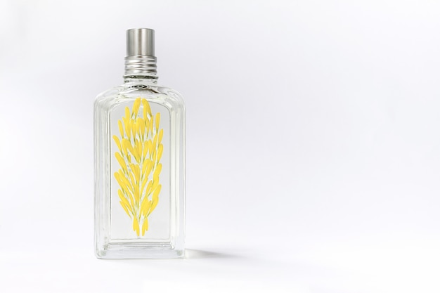 Transparent perfume bottle on white decorated with yellow flower petals Premium Photo