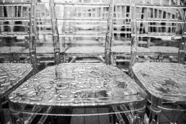 表面に雨の滴を透明なプラスチックの椅子、マクロ。クローズアップ-灰色の表面に水滴、webデザインと抽象的な背景テクスチャに使用します。 Premium写真