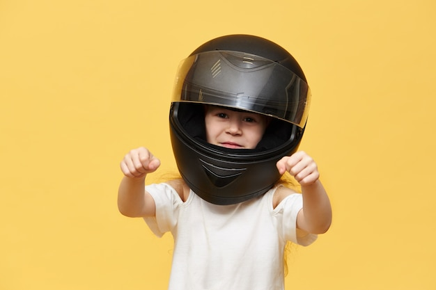 Transportation, extreme, motorsports and activity concept. portrait of dangerous little girl rider in black protective motorcycle helmet keeping hands in front of her as if driving motorbike Free Photo