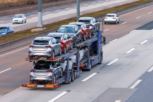 Transportation of new cars on a trailer with a truck for delivery to dealers. Premium Photo