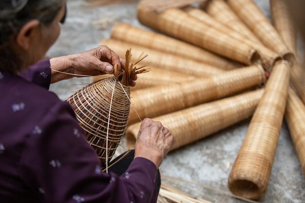 ベトナムのシニアは伝統的な竹の魚のtrapを作る職人です Premium写真