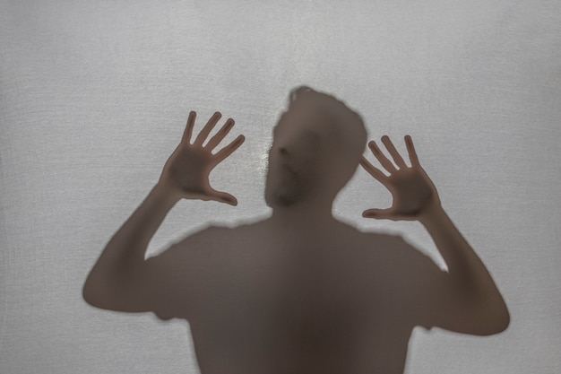 Trapped man screaming behind fabric Free Photo