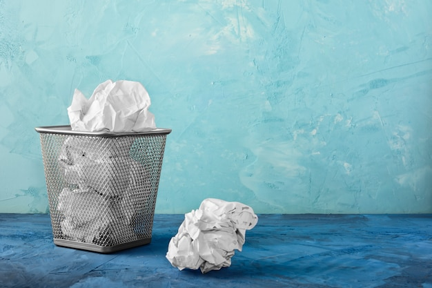 A trash can with papers, one lump is lying next to it. Premium Photo