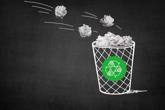 Trash with paper balls and a recycling symbol Free Photo