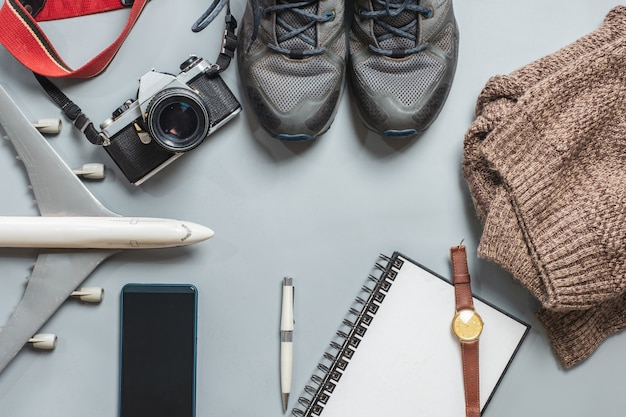Travel accessories with vintage camera, airplane, shoes, notebook, coat, on ba Premium Photo