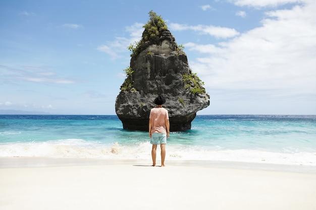 旅行、冒険、観光。ショートパンツ、tシャツ、海辺で瞑想の帽子をかぶって、石の島の前に立っているファッショナブルな裸足の男。美しい景色を眺めながらスタイリッシュな白人観光客 無料写真