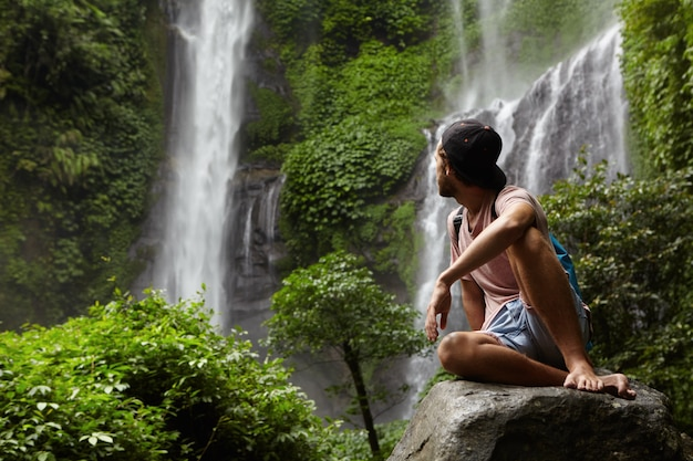 Travel and adventure. fashionable young man wearing snapback and backpack sitting on stone and looking back at waterfall in beautiful green rainforest. barefooted tourist having rest on rock in jungle Free Photo