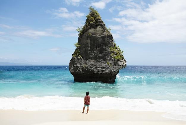 Концепция путешествий, приключений, хобби и отдыха. небрежно одетый молодой человек в черной шляпе идет по безлюдному песчаному пляжу, глядя на бирюзовый океан с каменным островом с высокими скалами посередине. Бесплатные Фотографии
