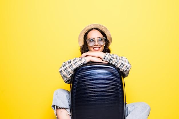 Концепция путешествий и образа жизни. портрет девушки в соломенной шляпе и солнечных очках с чемоданом, выглядящей изолированной Бесплатные Фотографии