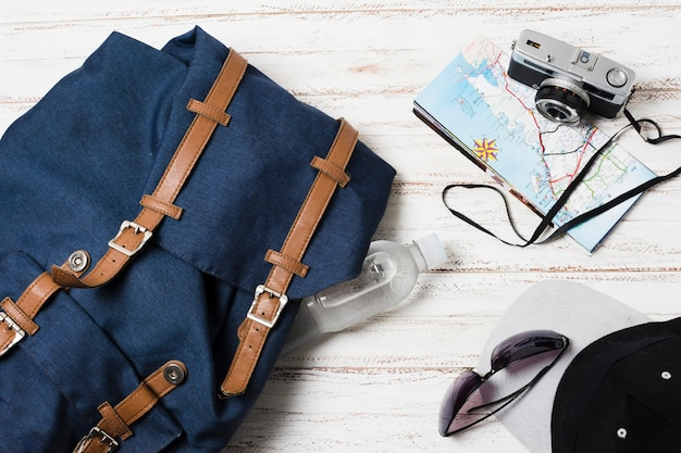 Travel bag and accessories on wooden background Free Photo