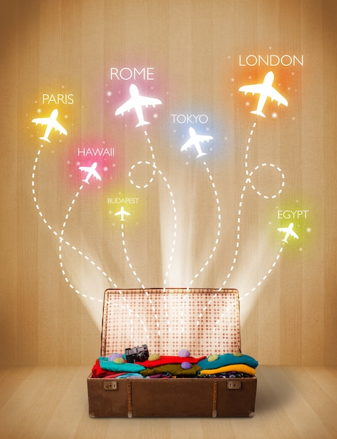 Travel bag with clothes and colorful planes flying out on grungy background Premium Photo