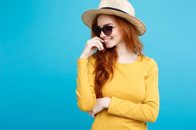 Концепция путешествия - закрыть портрет молодой красивый привлекательный рыжий рыжий волосы девушка с модной шляпе и солнцезащитные очки улыбается. голубой пастель фон. копирование пространства. Premium Фотографии