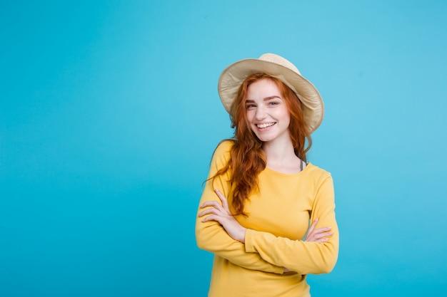 Concetto di viaggio - close up ritratto di giovane bella ragazza attraente redhair con cappello alla moda e sorridente sunglass. sfondo blu pastello. copia spazio. Foto Gratuite