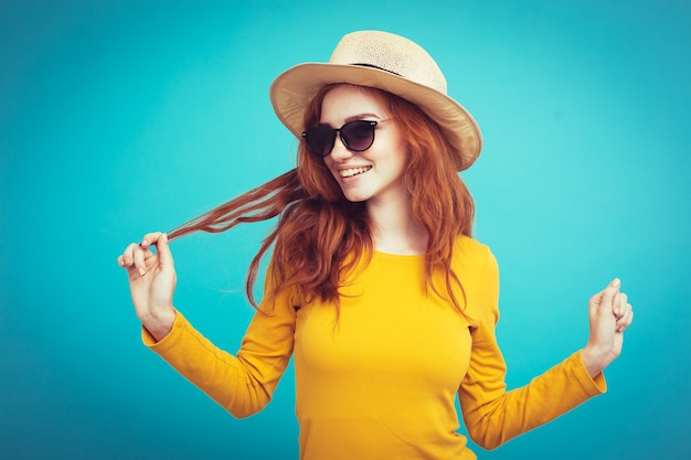 Travel concept - close up portrait young beautiful attractive redhair girl wtih trendy hat and sunglass smiling. blue pastel background. copy space. Free Photo