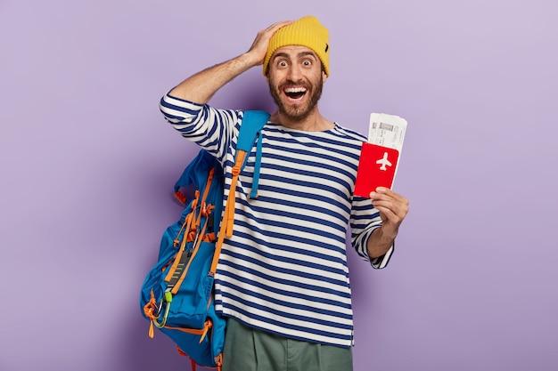 Concetto di viaggio. turista uomo felice si rallegra viaggio durante le vacanze estive posa con biglietto di viaggio e documenti organizza tutto per il viaggio trasporta zaino. backpacker ha atteso da tempo il viaggio Foto Gratuite