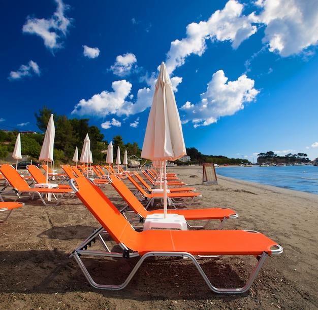 여행 컨셉-아름다운 해변, 자킨 토스 섬, 그리스에 우산과 일광욕 의자 프리미엄 사진
