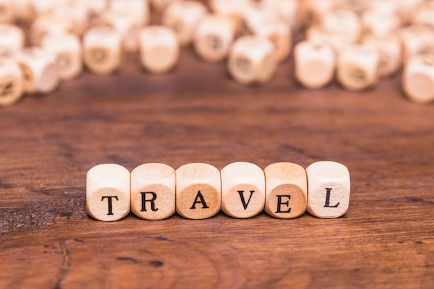 Travel concept with wooden cubes over brown table Free Photo