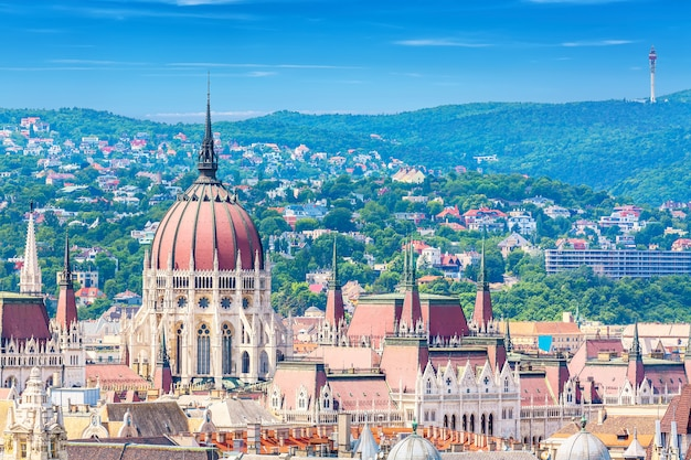 Travel and european tourism concept. parliament and buda side panorama of budapest in hungary during summer sunny day with blue sky and clouds. view from saint istvan's basil. Premium Photo