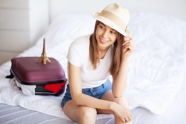 Travel. happy woman is packing suitcase at home Premium Photo