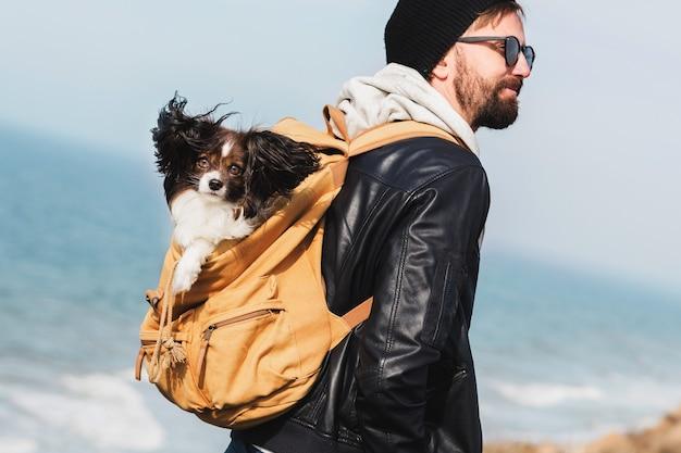 バックパックで犬と一緒に旅行の流行に敏感な男 無料写真