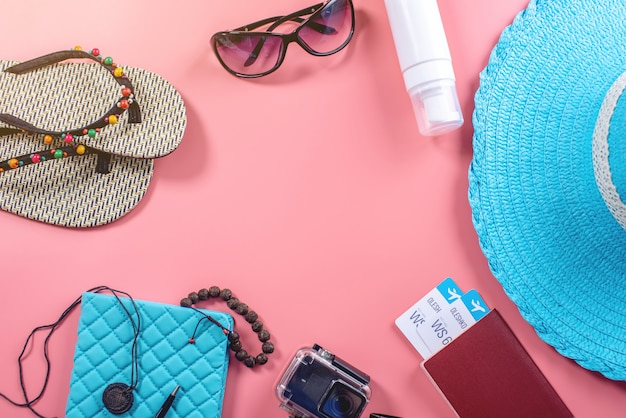 Travel holiday supplies: hat, sunglasses, camera passport and airline tickets on pink background Premium Photo