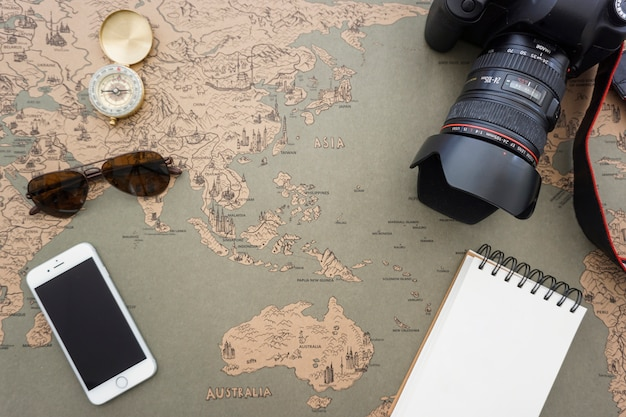 Travel items on vintage world map Photo