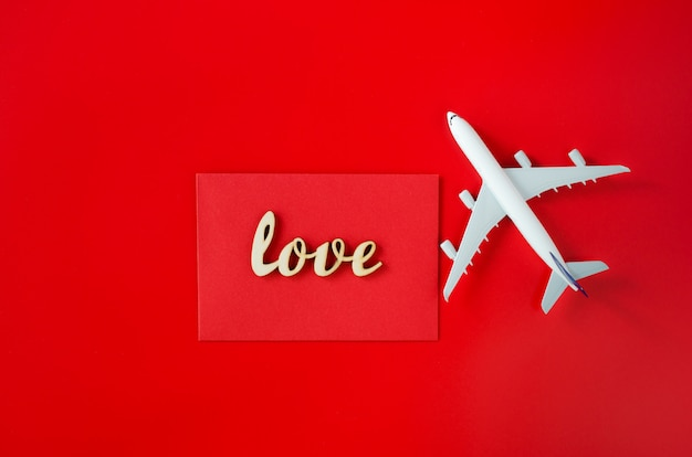 バレンタインデーの旅行計画。旅行のコンセプト。碑文の愛と赤い背景の旅客機のモデル。 Premium写真