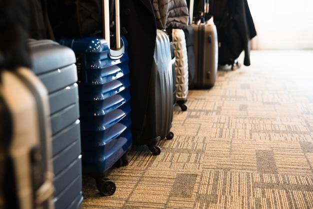 Туристические чемоданы выстроились в просторном гостиничном номере азиатских туристов, с копией пространства. Premium Фотографии