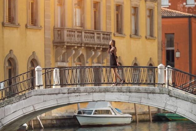 이탈리아 여행. 베니스에서 다리에 서있는 소녀. 아름 다운 단정 한 여자에 포즈를 취하는 프리미엄 사진