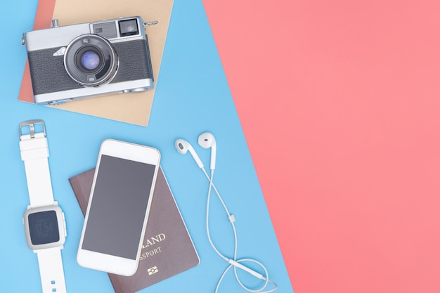 Travel top view gadgets and objects for business traveler on blue yellow pink copy space Premium Photo