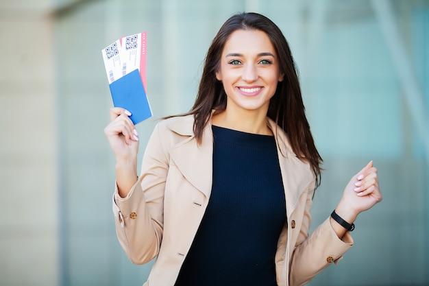 Travel. woman holding two air ticket in abroad passport near airport Premium Photo