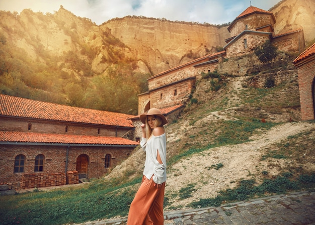 Travel woman posing against the backdrop of the mountains and medieval monastery. Premium Photo